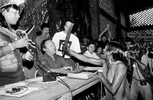 Observada por seu marido, Paulinho Paiakã, a Índia Kayapó Tuíra pasa o terçado (facão) no rosto de José Antônio Muniz Lopes, da Eletronorte, em protesto contra a construção da hidrelétrica de Kararaô, hoje Belo Monte. Foto histórica de Paulo Jares / A Província do Pará. 1989